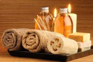 Beauty-Behandlung - Duftöle, Seifen und Schwämme mit Kerzen im Hintergrund